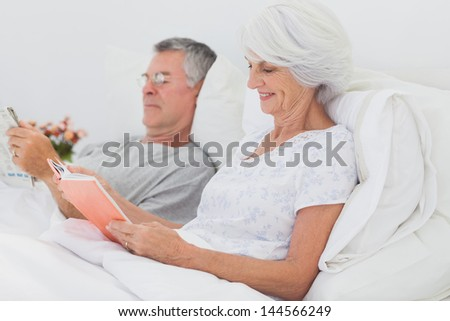 Mature couple reading together in bed