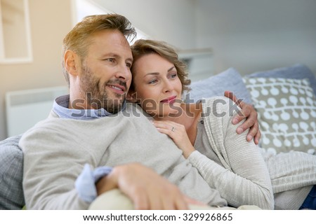 Mature couple relaxing in couch at home - stock photo