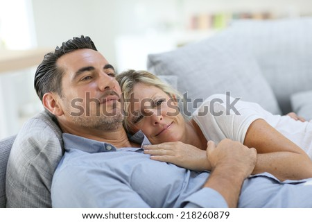 Mature couple relaxing in sofa at home - stock photo