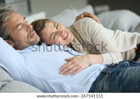 Mature couple relaxing in sofa, peaceful scene - stock photo