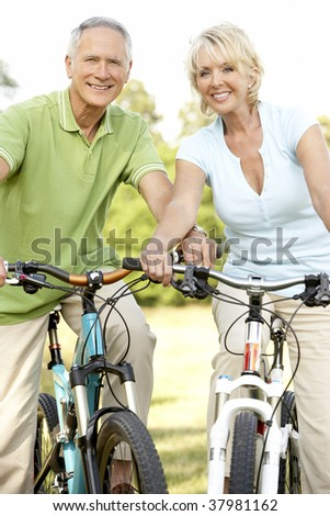 Mature couple riding bikes - stock photo