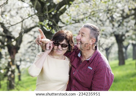 Mature couple runs under blooming cherry trees - stock photo