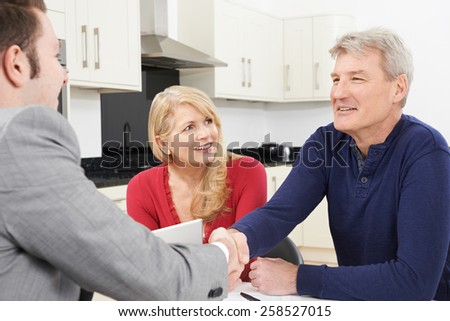 Mature Couple Shaking Hands With Financial Adviser At Home - stock photo