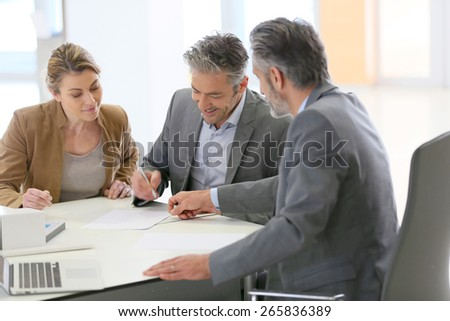 Mature couple signing construction contract in architect's office - stock photo