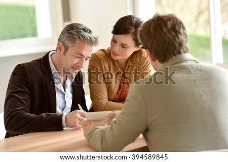 Mature couple signing documents in real-estate agency - stock photo