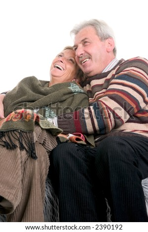 Mature couple sits on the couch, cuddles and laughs - stock photo