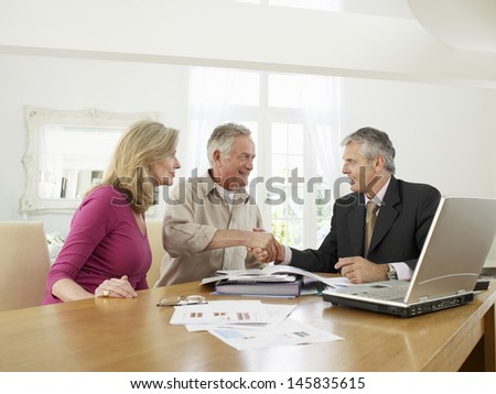 Mature couple sitting at table with financial advisor - stock photo