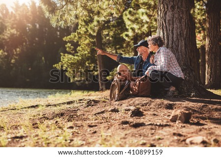Mature couple sitting by a tree in forest with man showing something to woman. Senior man and woman on a hike in nature on a summer day. - stock photo