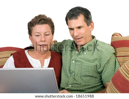 Mature couple sitting close working on the laptop computer - stock photo