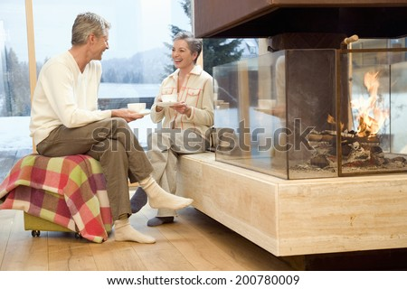 Mature couple sitting in front of fireplace holding tea cup - stock photo