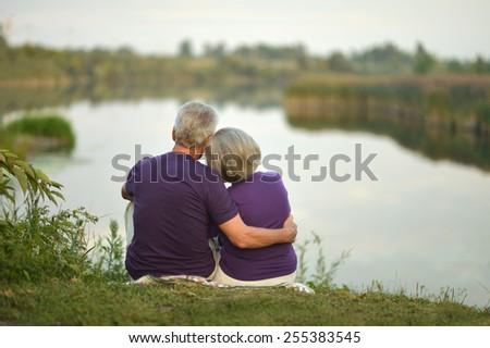 Mature couple sitting near lake,back view - stock photo