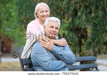 Mature couple sitting on bench outdoors