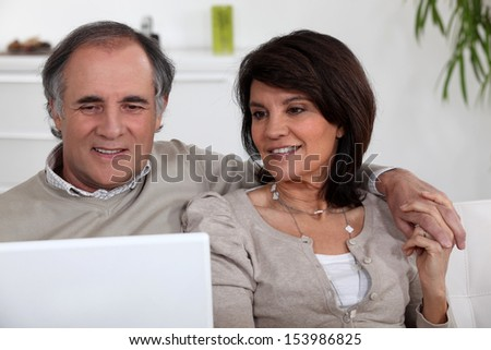 mature couple sitting on sofa with laptop - stock photo