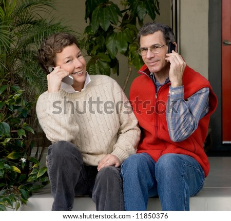 Mature couple sitting on their front porch, both talking on their cell phones - stock photo