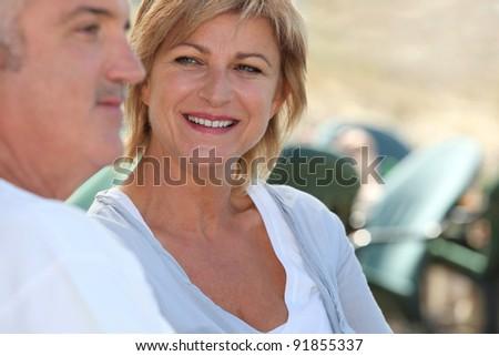 Mature couple sitting outside - stock photo