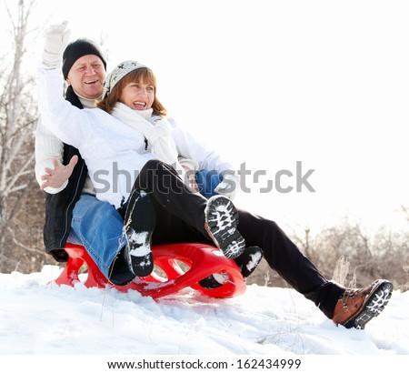 Mature couple sledding. Seniors couple on sled in winter park - stock photo