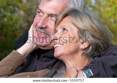 Mature couple smiling and looking sidewards. Focus on the woman - stock photo