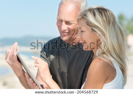 Mature couple smiling as they use a tablet on the beach with the woman surfing the net as the husband hand holds the computer - stock photo