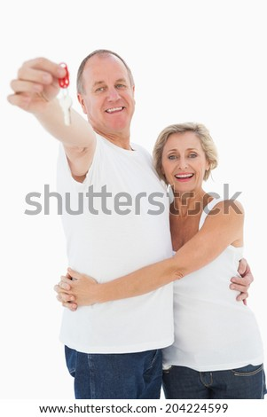 Mature couple smiling at camera with new house key on white background
