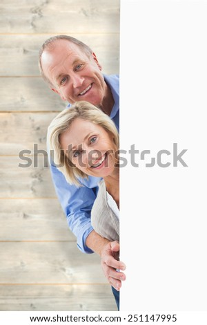 Mature couple smiling behind wall against pale wooden planks - stock photo