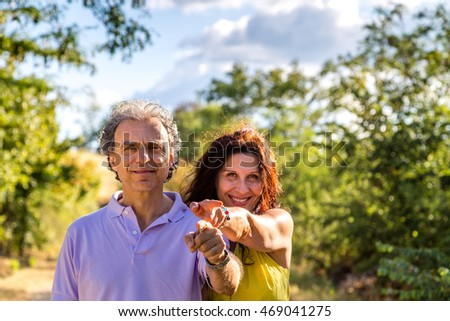 mature couple smiling pointing fingers in the countryside