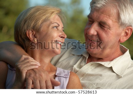 Mature couple smiling to each other. - stock photo