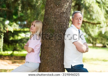 Mature couple standing against each other after a lovers tiff - stock photo