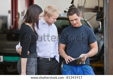 Mature couple standing with mechanic outside the garage - stock photo