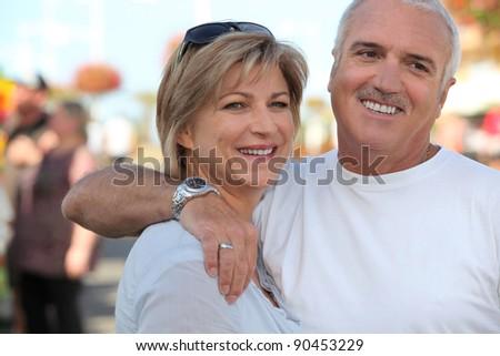 mature couple stood outdoors - stock photo