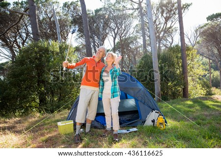 Mature couple taking a photo on their camp site - stock photo