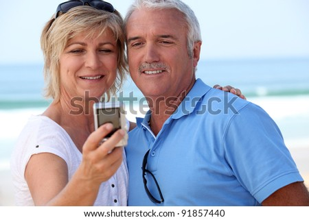 Mature couple taking a picture of themselves by the sea - stock photo