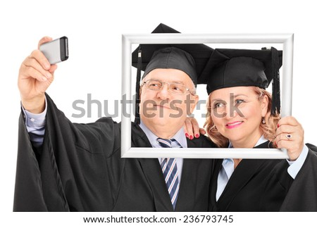 Mature couple taking a selfie behind a picture frame isolated on white background - stock photo