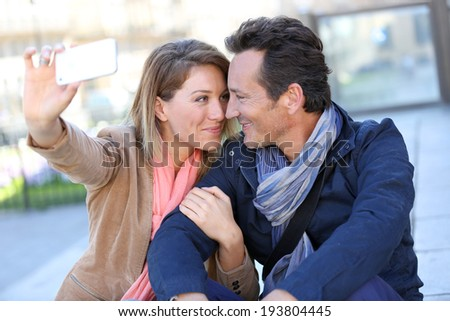 Mature couple taking picture with smartphone - stock photo