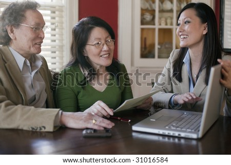 Mature couple talking to financial planner at home - stock photo