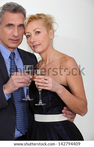 Mature couple toasting with champagne - stock photo