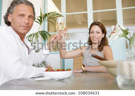Mature couple toasting with champagne and eating strawberries, smiling. - stock photo