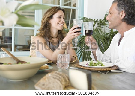 Mature couple toasting with red wine while having lunch at their vacation home. - stock photo