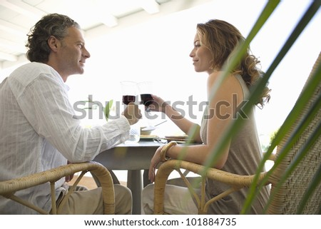 Mature couple toasting with red wine while having lunch in a hotel. - stock photo