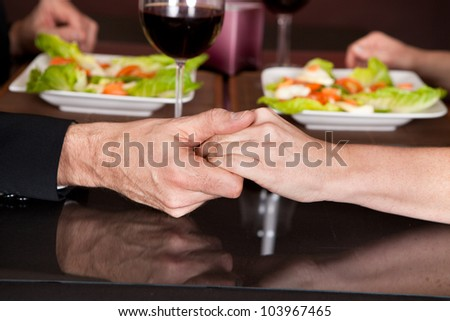 Mature couple touching hands at romantic dinner in restaurant - stock photo