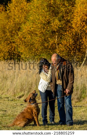 Mature couple training retriever dog autumn walk in sunset park - stock photo