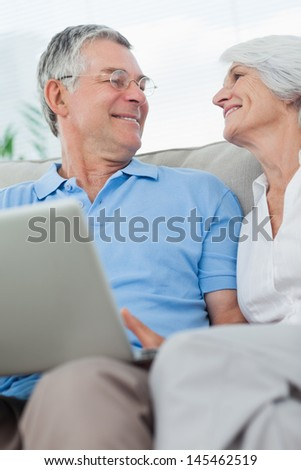 Mature couple using a laptop pc on the couch - stock photo