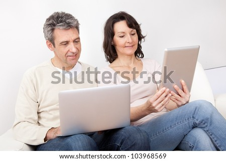 Mature couple using laptop and tablet in couch at home - stock photo