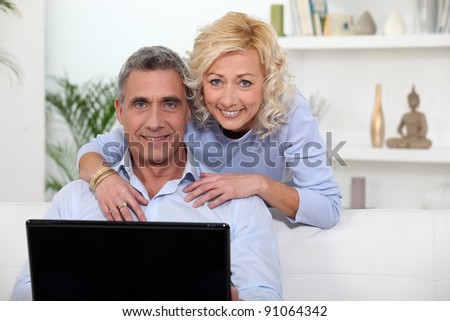 Mature couple using laptop at home - stock photo