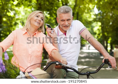 Mature couple using mobile phone during riding on the bike