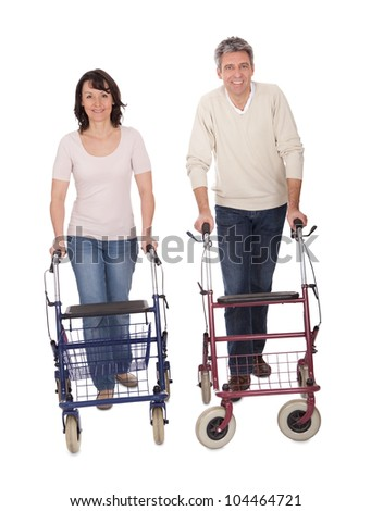Mature couple using walking aide. Isolated on white