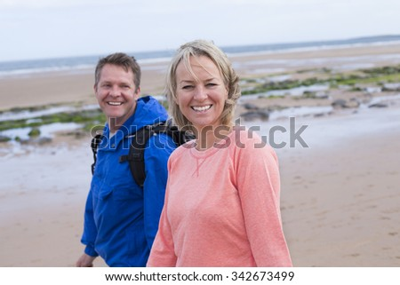 Mature Couple walking along the beach. They are wearing casual clothing and smiling at the camera.  - stock photo