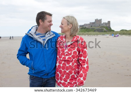 Mature Couple walking along the beach. They have their arms around each other and a castle can be seen in the background.  - stock photo