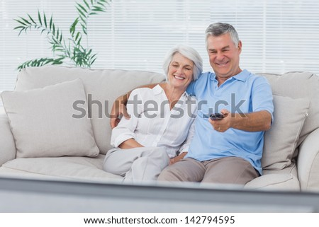 Mature couple watching television sitting on the couch - stock photo