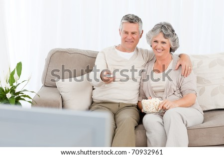 Mature couple watching tv in their living room at home - stock photo
