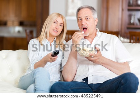 Mature couple watching tv while eating pop corn at home